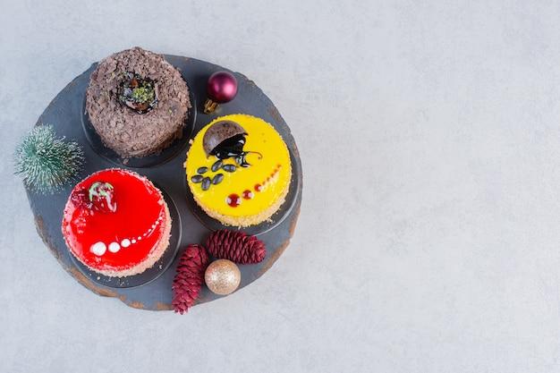 Divers gâteaux sur tableau noir avec des ornements de noël.