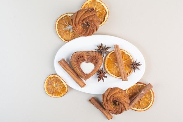 Divers gâteaux avec tranches d'orange, clous de girofle et cannelle sur plaque blanche
