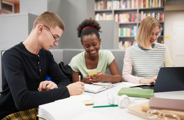 Divers groupes de jeunes qui étudient ensemble à table dans la bibliothèque du collège se concentrent sur les étudiants masculins...