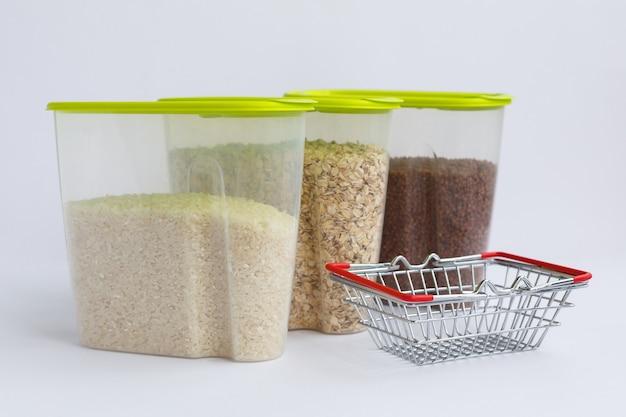 Divers gruaux dans des récipients ou des bocaux sur fond blanc et un panier d'épicerie