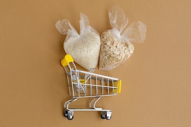 Divers gruaux en paquets dans le chariot d'épicerie riz et flocons d'avoine