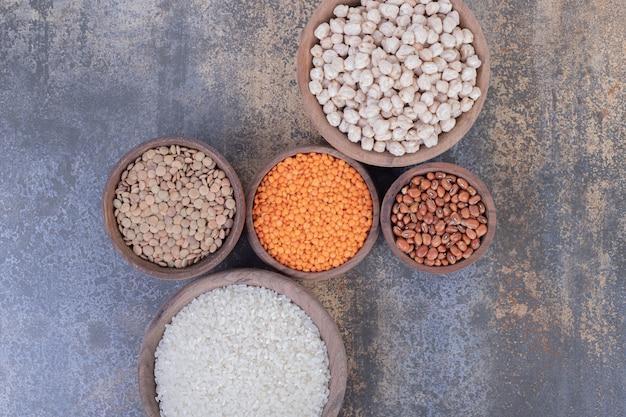 Divers haricots crus, lentilles et riz dans des bols en bois.