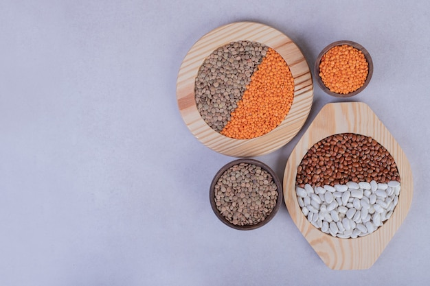 Divers haricots et lentilles crus dans des bols en bois.