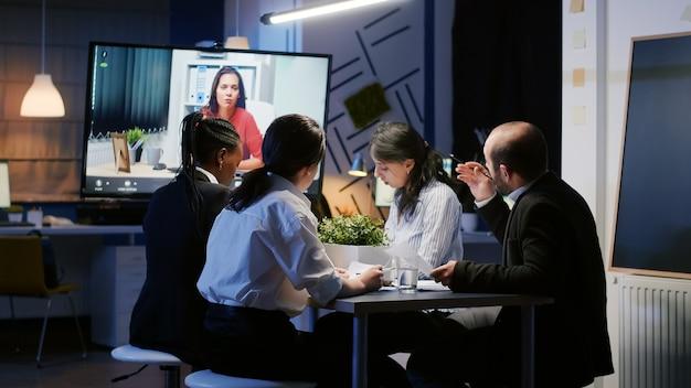 Divers hommes d'affaires multiethniques discutant avec un entrepreneur à distance lors d'une conférence vidéo en ligne tard dans la nuit dans la salle de réunion. idées de brainstorming de travail d'équipe ciblé