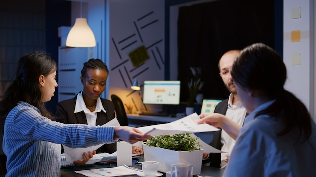 Divers hommes d'affaires multiethniques partageant des graphiques de gestion surchargés de paperasse lors d'une réunion de bureau...