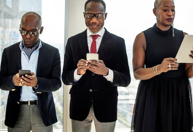 Divers hommes d'affaires utilisent des appareils numériques