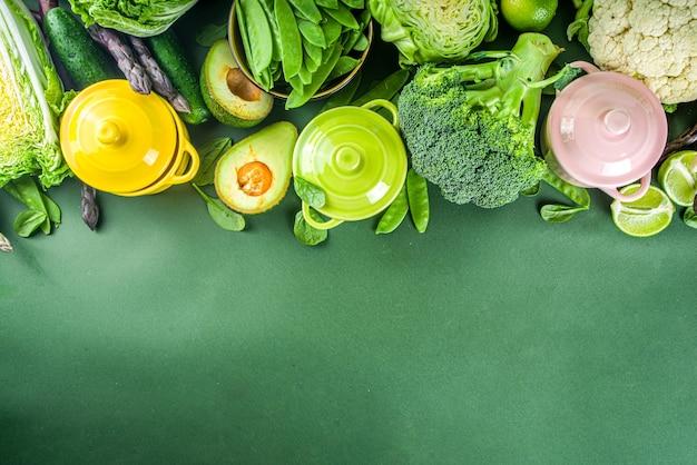 Divers ingrédients végétaux de printemps verts biologiques avec des marmites portionnées colorées vides sur une table de cuisine vert foncé, vue de dessus. soupe saine de régime, concept de préparation de ragoût de nourriture
