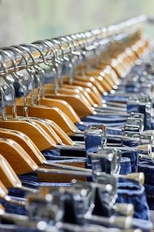 Divers jeans bleus sur une penderie dans le magasin de vêtements