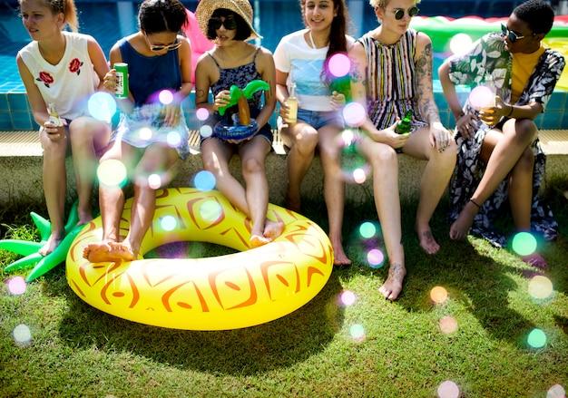 Divers jeune adulte buvant au bord d'une piscine