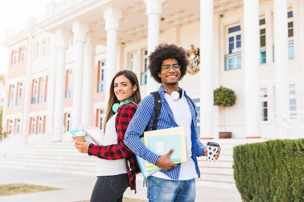 Divers jeunes étudiants et étudiantes tenant des livres et une tasse de café à emporter debout devant le bâtiment