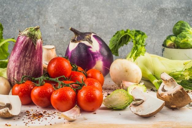 Divers légumes biologiques et flocons de piment rouge sur une table en bois