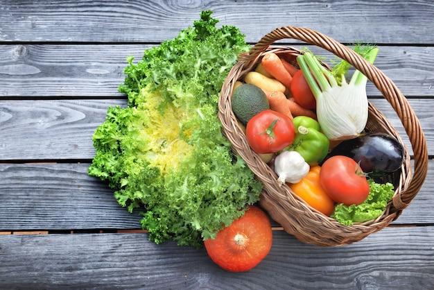 Divers et légumes colorés dans un panier en osier mis sur une table en bois à côté