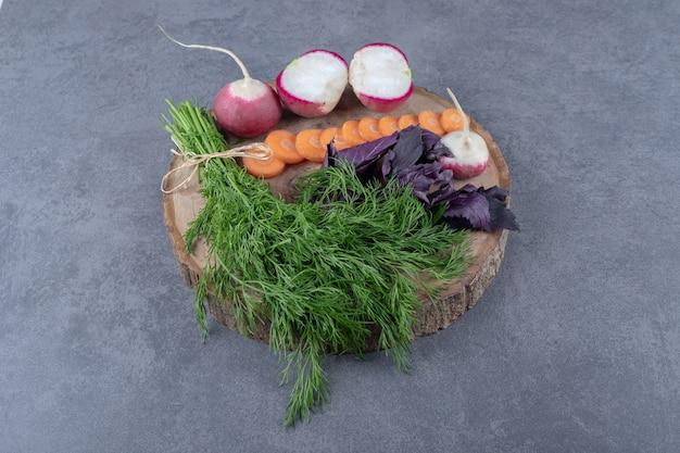 Divers légumes dans une planche, sur la surface en marbre.