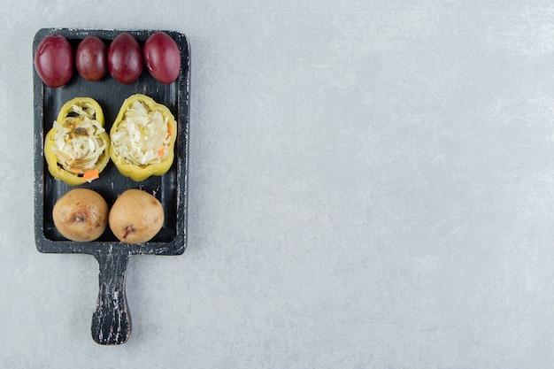 Divers légumes fermentés sur tableau noir.