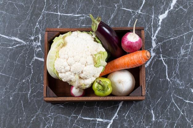 Divers légumes frais sur boîte en bois.