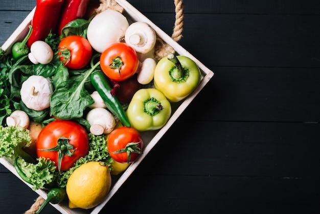 Divers légumes frais dans un récipient sur une surface en bois noire