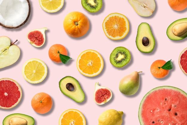 Divers légumes et fruits sur une surface rose.