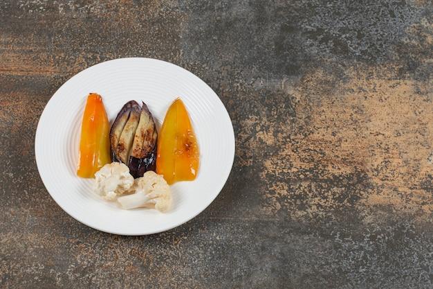 Divers légumes grillés sur plaque blanche.