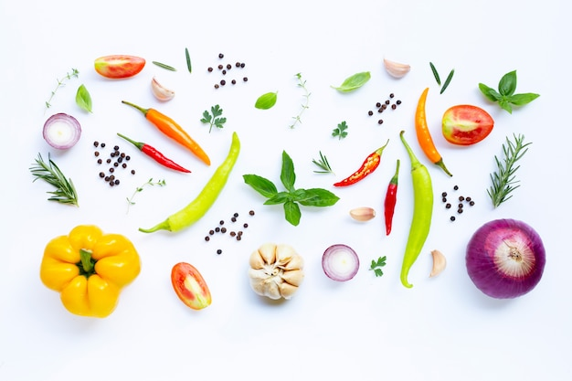 Divers légumes et herbes fraîches sur fond blanc.
