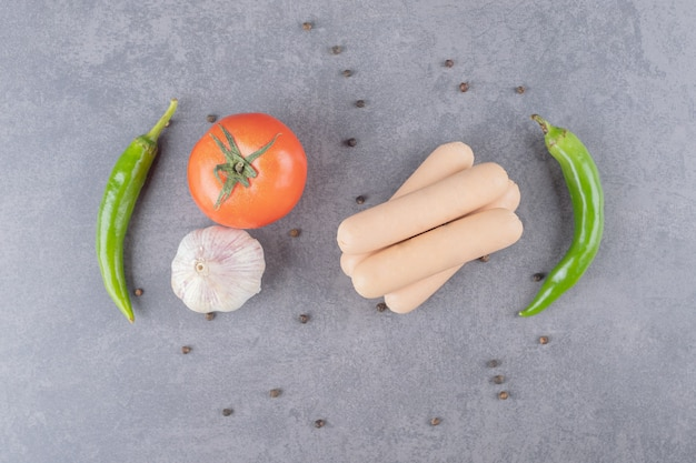 Divers légumes avec des saucisses sur une surface en marbre