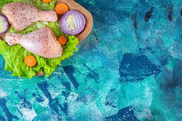 Divers légumes en tranches et pilons de poulet marinés sur la planche à découper