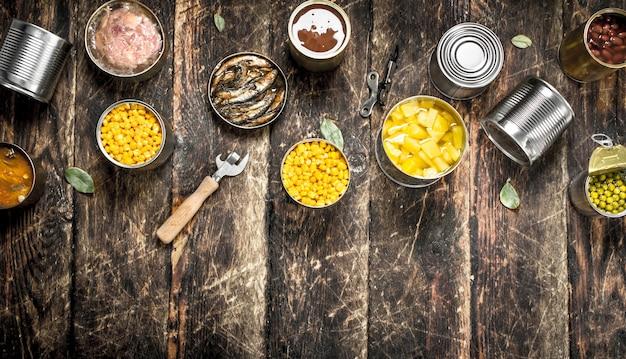 Divers légumes, viande, poisson et fruits en conserve dans des boîtes de conserve. sur un fond en bois.