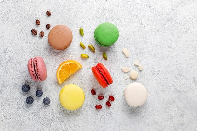 Divers macarons aux pistaches, fruits, baies, grains de café.