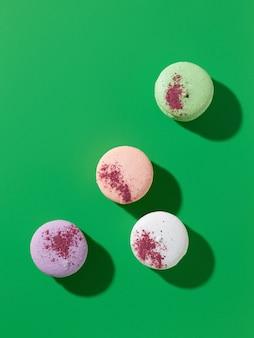 Divers macarons français décorés de poudre végétale colorée sur fond vert, vue de dessus