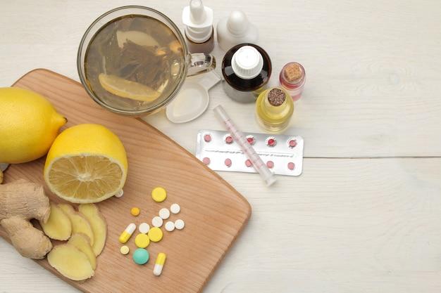 Divers médicaments contre le rhume et remèdes contre le rhume sur une table en bois blanche.