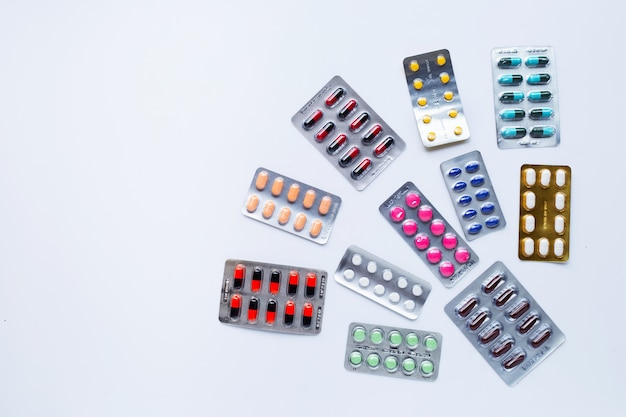 Divers médicaments en gélule, pilules et comprimés sous blister sur fond blanc