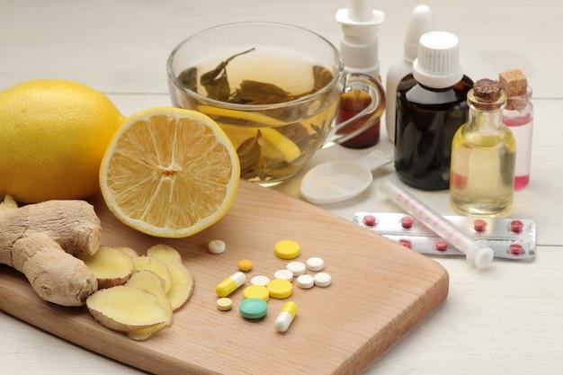 Divers médicaments pour la grippe et les remèdes contre le rhume sur une table en bois blanc
