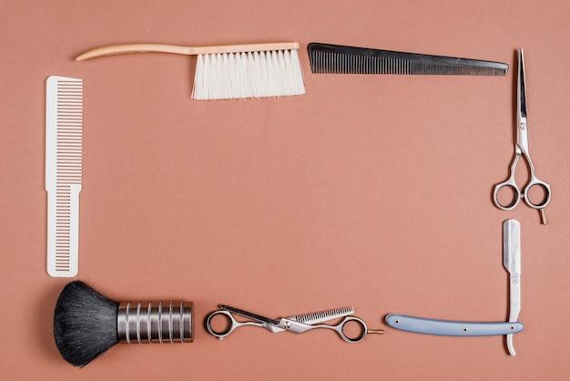 Divers outils de coiffeur formant cadre sur fond coloré