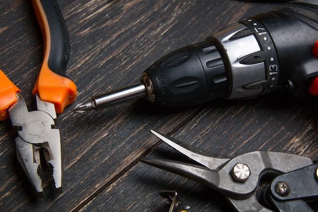 Divers outils de travail sur une table en bois sombre.