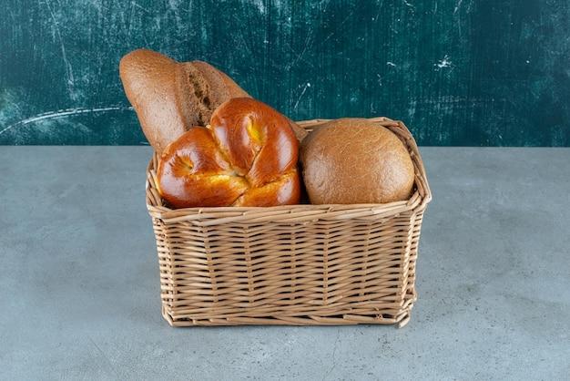 Divers pains et pâtisseries dans un panier en bois.