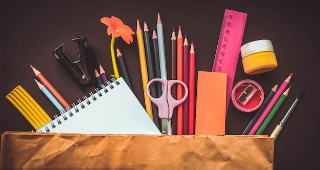 Divers papeterie dans un sac en papier sur fond marron. fournitures scolaires papeterie, crayons de couleur, peintures, papier sur fond marron, concept de retour à l'école, éducation élémentaire moderne. mise à plat.