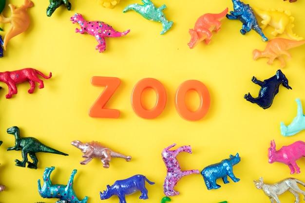 Divers personnages de jouets animaux fond avec le mot zoo