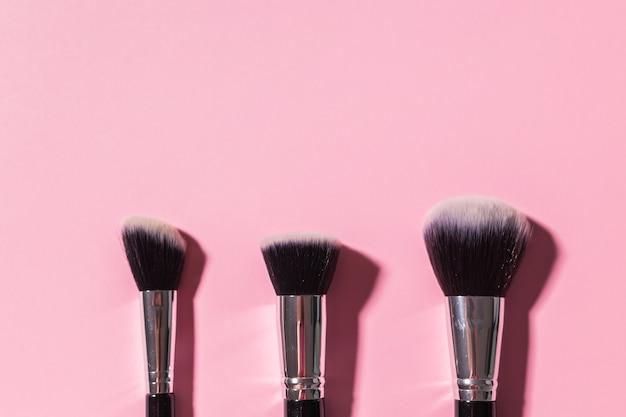 Divers pinceaux de maquillage sur fond rose avec copie espace vue de dessus cosmétiques et concept de beauté