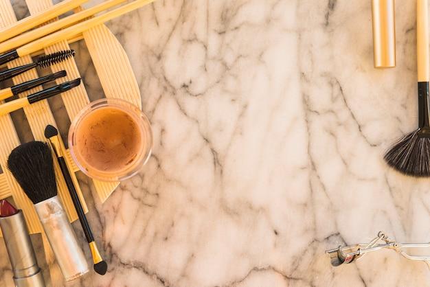 Divers pinceaux de maquillage; mascara; miel avec recourbe-cils sur fond de marbre