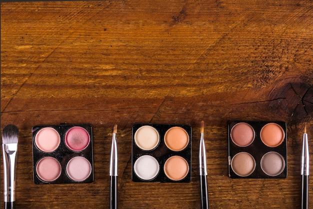 Divers pinceaux de maquillage et poudres d'ombres à paupières colorées sur fond de bois