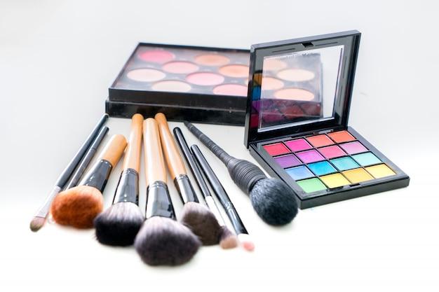 Divers pinceaux de maquillage avec des produits de maquillage