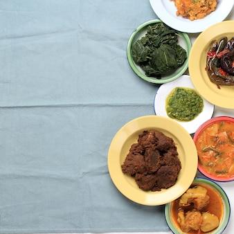 Divers plats de padang appelés masakan padang ou padang plats. plats populaires en indonésie originaire de minang, à l'ouest de sumatra, servent sur une couche d'assiettes empilées sur fond blanc