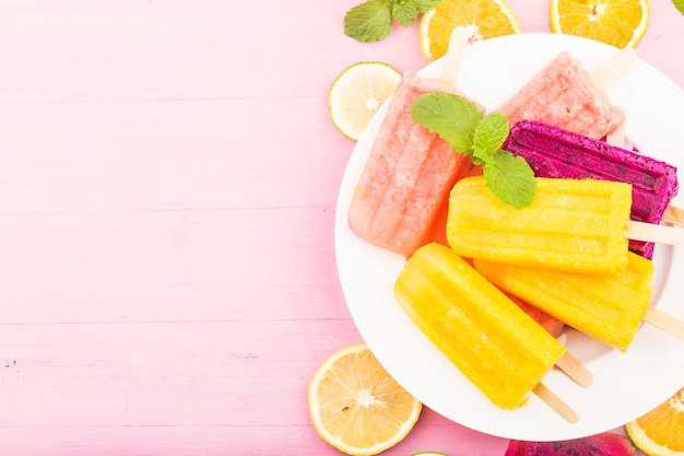 Divers popsicles de fruits frais placés sur fond de planche de bois