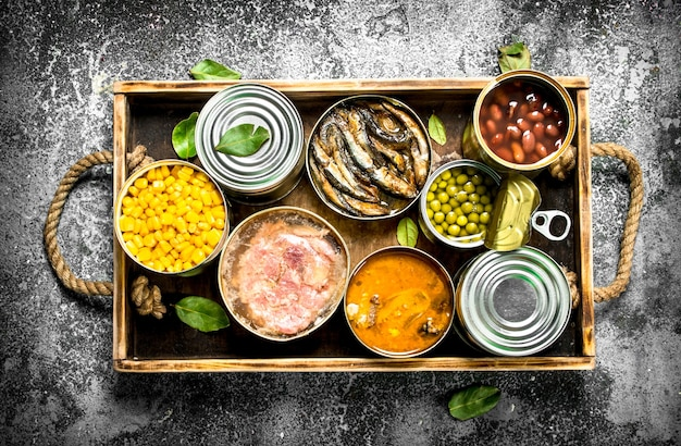 Divers produits en conserve dans des boîtes de conserve sur un plateau en bois sur un fond rustique