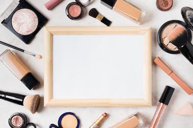 Divers produits cosmétiques et cadre vide dispersés sur fond clair
