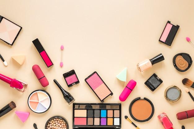 Divers produits cosmétiques dispersés sur une table beige