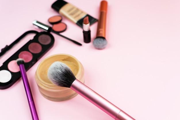 Divers produits cosmétiques sur fond rose