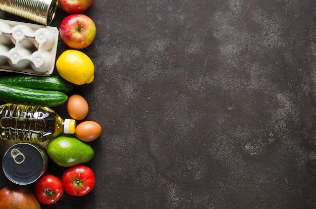 Divers produits d'épicerie sur fond de béton foncé. concept de livraison de nourriture. dons de nourriture.