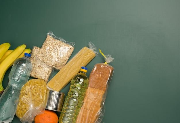 Divers produits, fruits, pâtes, huile de tournesol dans une bouteille en plastique et conservation, vue de dessus. concept de don, espace copie