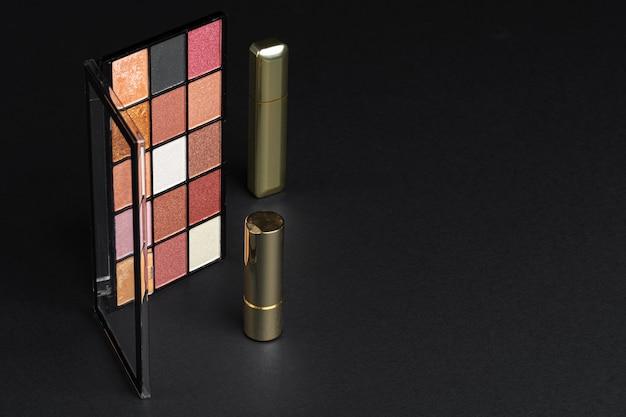 Divers produits de maquillage sur fond de texture noir.