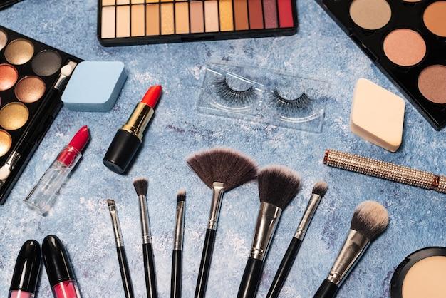 Divers produits de maquillage, pinceaux sur fond bleu